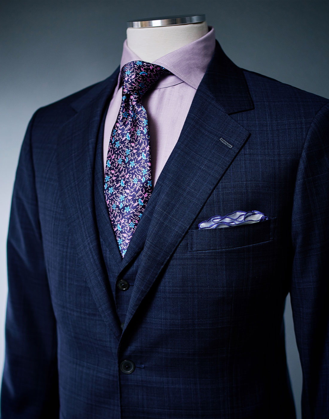 Men's bespoke suit jacket with a purple tie